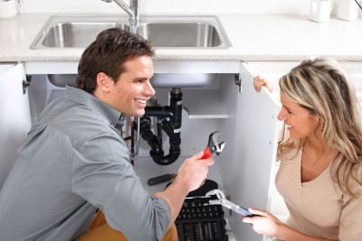Irving TX plumber talks with a customer during a sink drain repair