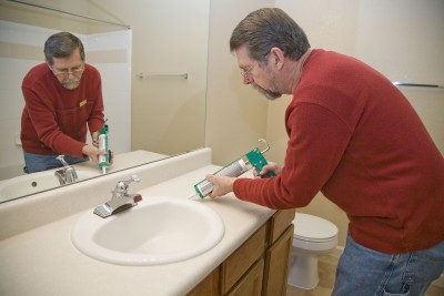 Plumber carefully caulks a sink after a new installation